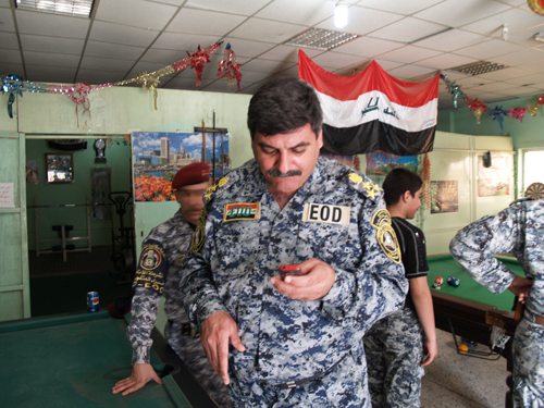 An Iraqi officer in uniform watches the screen of his cell phone in the recreation room of the General Counter Explosive Directorate.