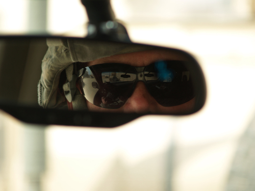 The sunglasses of a soldier are visible in his rearview mirror.