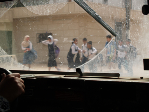 A view of a Baghdad street through a dirt-caked windshield.