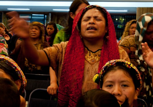 An indigenous Mayan woman prays and sings during a fiery Evangelical Sermon at El Calvario Church