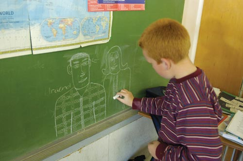 Ginger-Haired Boy Draws on Chalkboard