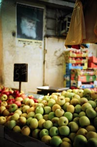 A stand is piled high with apples, plastic grocery bags hang overhead. Behind is a wall, high on which is a poster of a glowering, bearded face.