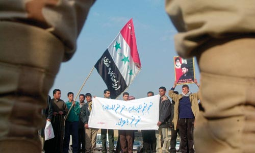 A small group of Iraqi men line a street, holding a banner and an Iraqi flag.