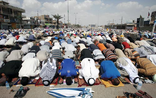 Hundreds of men bow, at prayer, touching their heads to the rugs beneath them. They are outside.