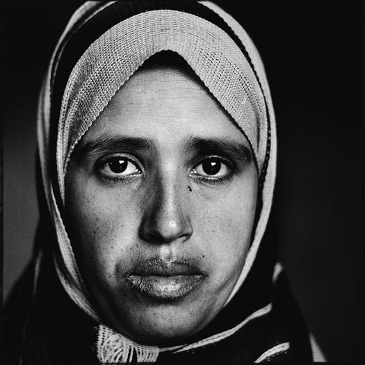 A younger woman with a headscarf and full lips.
