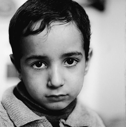A young boy, his head tilted downward, looks up at the camera.