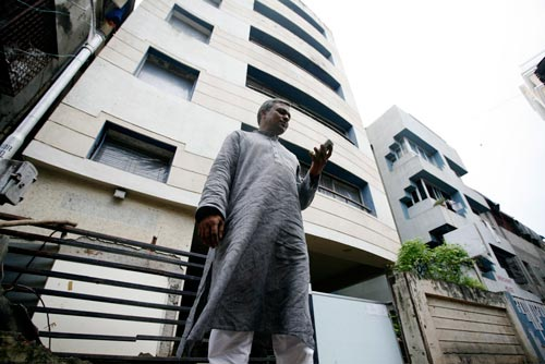 Standing next to a six-story building, a man looks at his mobile phone. He's wearing a kurta, a knee-length shirt not unlike a nightgown.
