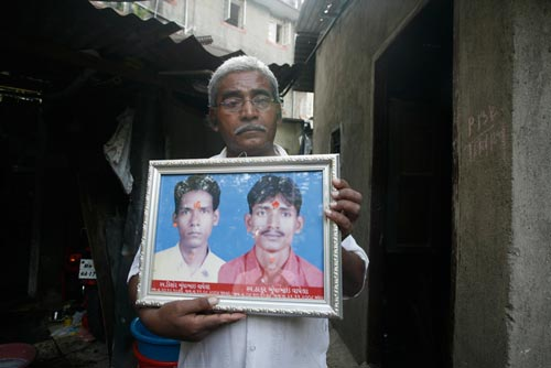 A middle-aged man stands outside of a ramshackle garage, holding a large, framed portrait of a pair of young men. He looks sad.