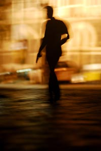 Seen in a blurred silhouette, a man walks down a street, holding a handgun at his side. It is daytime, and he is backlit.