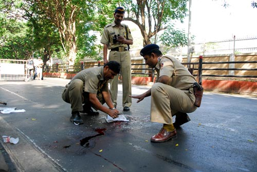 Three khakied police officers attend to a crime scene, in the form of a pool of blood in a street. Some of it has run downhill in a rivulet.