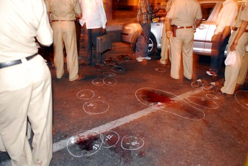 Nine people stand in and around a crime scene on an urban street. A series of numbers chalk circles on the asphalt mark apparent evidence, including bloodstains and a pair of shoes. It is nighttime.