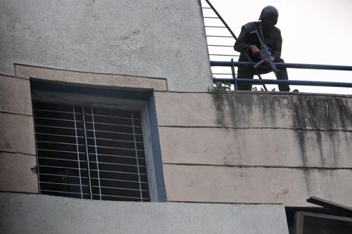 A soldier, clad all in black with a helmet and a face covering, leans over a railing on a balcony, looking down while clutching a Heckler & Koch MP5 assault weapon.