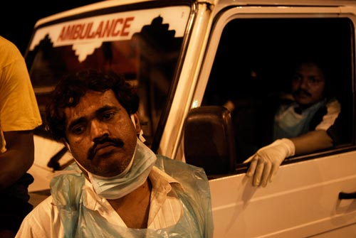A dejected-looking man stands in front of an ambulance. A surgical mask is looped around his ears, but it's pushed down under his chin. He wears a disposable plastic smock.