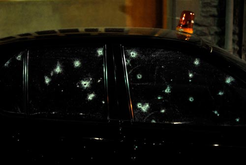 A black police car with darkly tinted windows is riddled with bullet holes. A red siren, intact, perches atop the roof.
