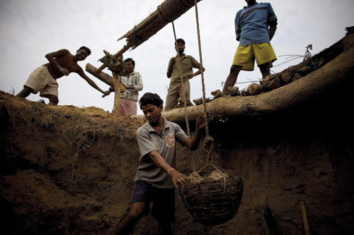 Men improvise a winching system to illegally gather coal from a pit in Jharia.