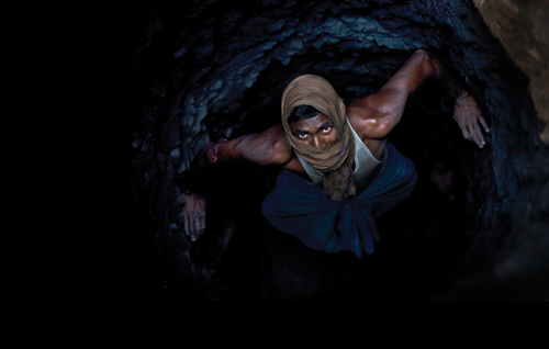 A man crawls through a deep mine. The constant coal fires in Jharia send underground temperatures soaring.