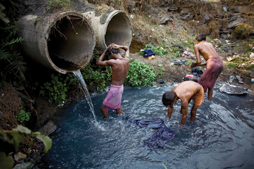 Young men bathe and wash their clothes after a day of scavenging coal.