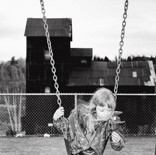 Lola Angus on a swing in the grade school playground adjacent to the Right of Way Mine property, Cobalt, Ontario.