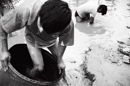 A mineworker climbs barefoot into a barrel filled with sediment and mercury.