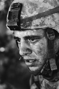 A dirty, sweaty, stunned-looking soldier, staring at something off-frame.