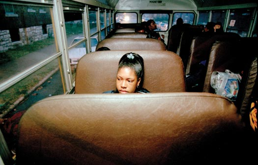 A girl sits alone on the brown pleather seat of a school bus, looking out the window. She's one of just a handful of students on the bus. It is twilight outside.