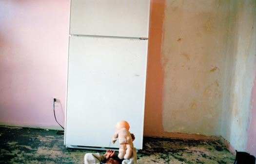 A bare room, old pink and white paint splotched on the walls, green paint peeling up from the floors. The only object within it is a lone refrigerator. A young child lies on her back on the floor, playing with a naked doll.