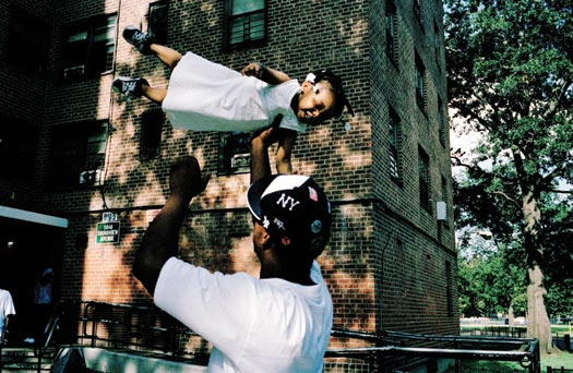 A man wearing a Yankees cap tosses a toddler into the air as she laughs. The toddler is wearinga white dress and tiny sneakers. Behind them is a large, brick public housing complex.