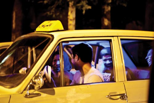 A yellow taxi is full of laughing young adults. A young man drives, a smiling young woman sitting next to him.