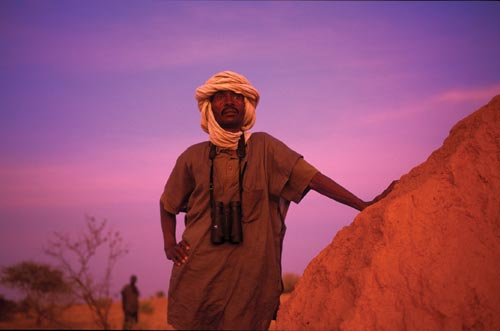 A moustached man leans against a rock, looking into the distance. His head is wrapped in a white scarf. A pair of binoculars hang around his neck. The sun, presumably low on the horizon, gives everything a reddish cast.