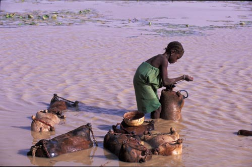 Standing in shin-high muddy water, a girl is surrounded by bags that she's filling with water. Each of the bags is othing more than the skin from the body of an animal, the legs tied off with rope.