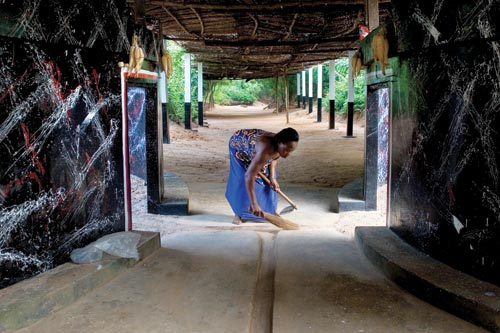 A woman wearing a blue dress stoops over while sweeping a dirt floor. She's surrounded by the cement walls and thatched roof of a shrine.