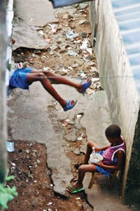 Two children sit in a trash-strewn alley. Both wear shirts and plastic sandals. One is eating out of a white, plastic bowl.