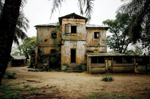 A once-grand home that looks long past its prime. The doors and windows are gone, the roof is coming off, and weeds are growing out of the walls. The walls have weathered to a splotchy orange and white. It is surrounded by a dirt yard.