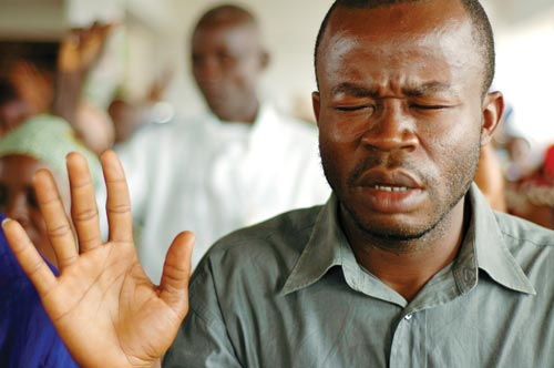A man stands among others, eyes squeezed shut in prayer, hands raised with his palms open. Unshaven, he wears a light green button down shirt, open at the collar.
