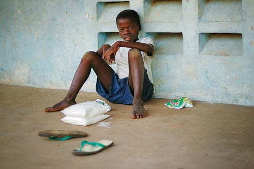 A young boy sits on a brown cement floor, leaning against a pale blue cement wall, legs sprawling out before him. He's taken off his sandals. Around him are several bags full of white powder. He looks directly at the camera.
