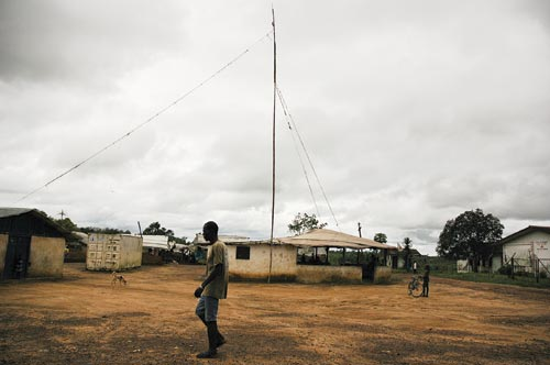 Amidst low, sparse, beige buildings is one, which stands out because it has an antenna standing next to it. The antenna is not very straight, perhaps made out of branches; several guy-wires hold it upright. Several people can be seen in the packed-dirt street that surrounds the building, along with a dog.