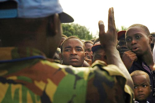A scrum of males of all ages press together to listen to a man, who faces away from the camera. He wears camouflage, and gesticulates while apparently addressing them.