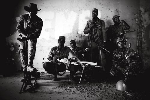 Half a dozen soldiers pose for a photograph. They are heavily armed, half of them with ammunition slung over their shoulders. One wears a cowboy hat, shielding his eyes from the camera. All are wearing military uniforms, some camouflaged.