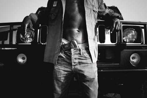 A man stands in front of a Hummer, posing as if for the cover of a rap album. He is photographed from the chest down to the knees. His button-down shirt is open in the front, revealing high-riding boxers and a handgun stuffed into the waist of his stylish jeans. The grill of his vehicle is polished to a high shine.