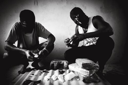 A pair of masked men process bricks of drugs, breaing off pieces and wrapping them up for sale on a smaller scale. They each wear ski masks. One of them wears a t-shirt promoting Ohio Girls Basketball.