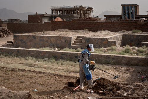 An Afghan de-miner painstakingly searches for landmines