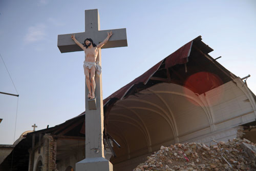 A crucifix stands in front of a pile of rubble from a demolished building.