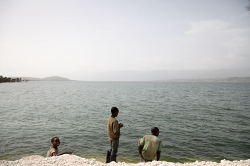 Three young Hatian boys stand on a rocky white beach above the ocean.
