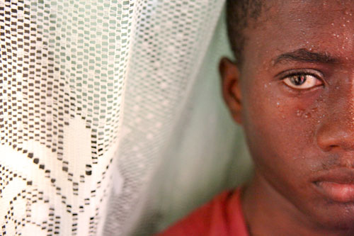 A closeup of a young Hatian boy in a red t-shirt. He is flanked on one side by a lacy white curtain.