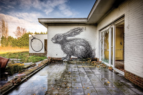 An abandoned house with broken sliging glass doors with a giant rabbit graffittied onto the wall.
