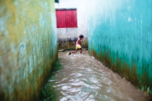 A child runs through a rush of water flowing between buildings after a downpour.