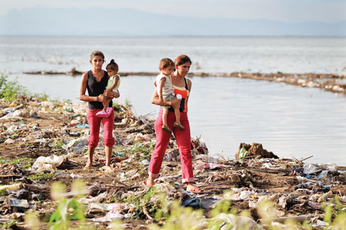 Edda Montes, right, and her teenage daughter Tatiana walk the lake's edge with their children in their arms.