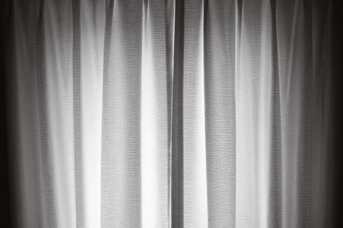 A black and white image of a window with light illuminating the curtains from outside.