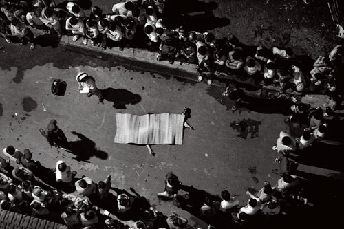 Seen from above, a circle of people crowd around a body which lies on the pavement covered by a blanket.