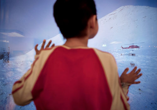 A helicopter arrives in Siorapaluk, Greenland's northernmost settlement, while Asiaq, eight, watches from his classroom window.